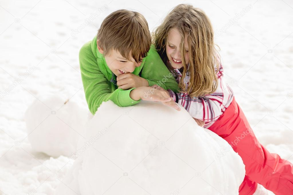 young boy and girl building a snowman