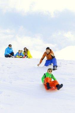 Family sledding in winter stock vector