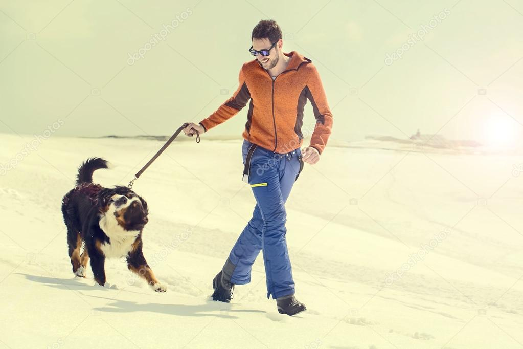 Man and his dog running in the snow