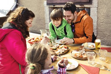 Family having lunch in a chalet in mountain