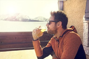 Seated and relaxed man drinking a beer in peace