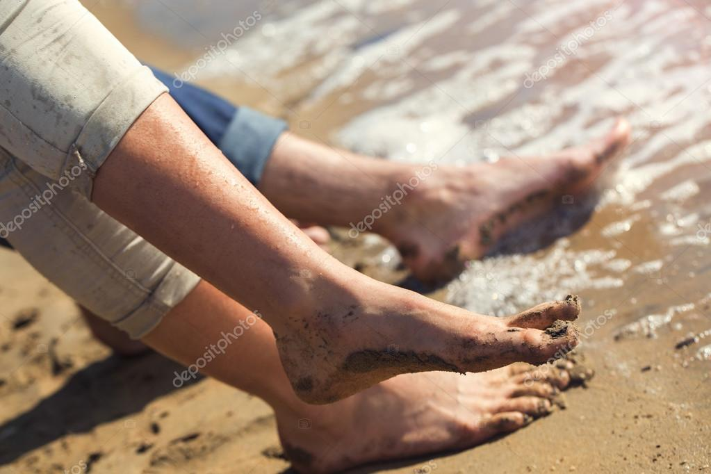 Pair of feet splashing in the water to the sea