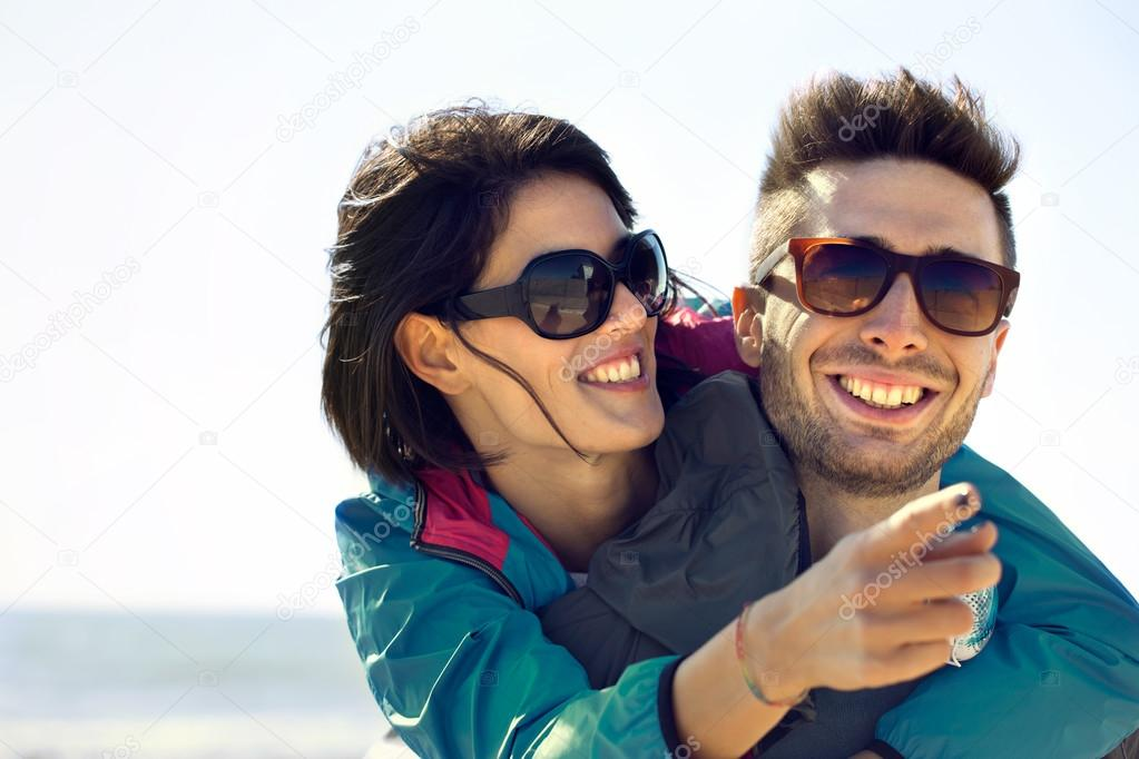Young woman shows her man the Sea View, happy couple having fun at sea