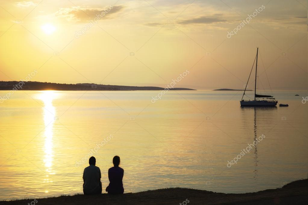 backlit couple admiring the sunrise over the sea