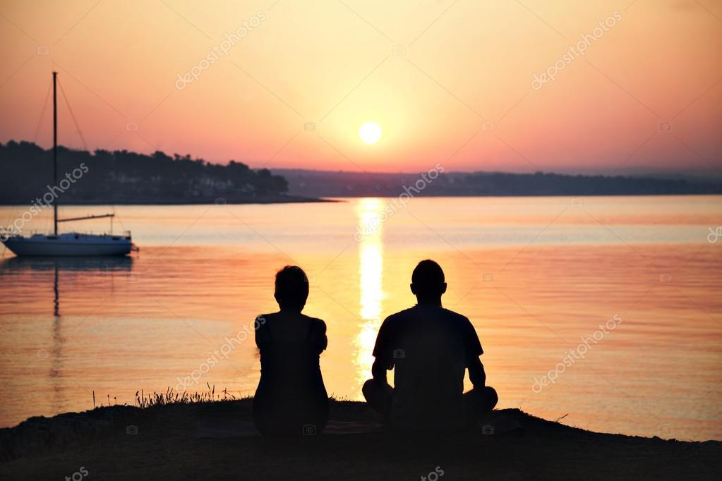 backlit couple admiring the sunrise over the sea
