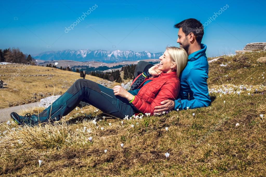 Two hikers with backpack resting on the mountain top