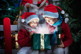Two children opening Christmas gift with rays of light