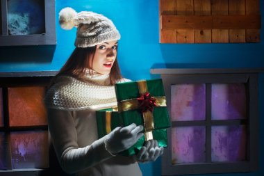 young woman opens her gift Christmas in a magical atmosphere