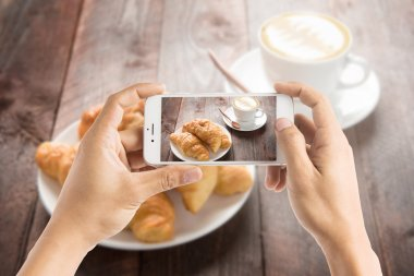 Taking photo of fresh baked croissants and coffee on wood table