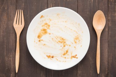 Empty dish after food on the wooden background