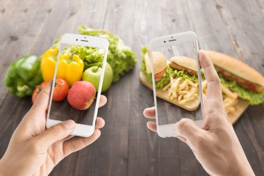Friends using smartphones to take photos with contrasting food.