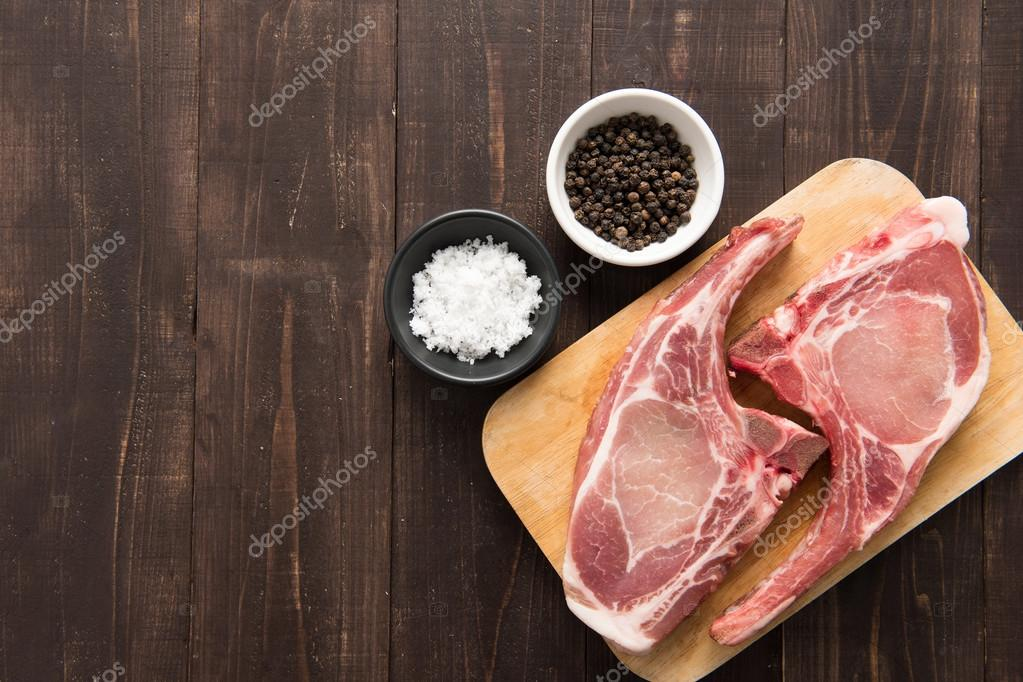 Fresh pork chops with pepper and salt on wooden background
