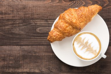 Coffee cup and fresh baked croissants on wooden background. Top