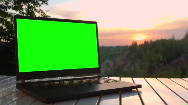 Fekete laptop zöld képernyővel van egy összecsukható asztalon naplementekor a hegy tetején.