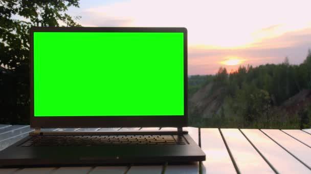 Schwarzer Laptop mit grünem Bildschirm liegt bei Sonnenuntergang auf dem Gipfel des Berges auf einem Klapptisch.