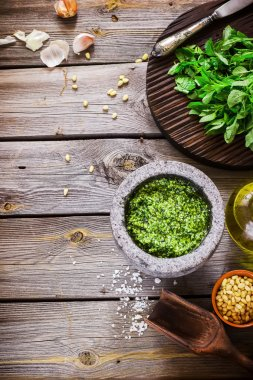 Pesto and ingredients on wooden table.