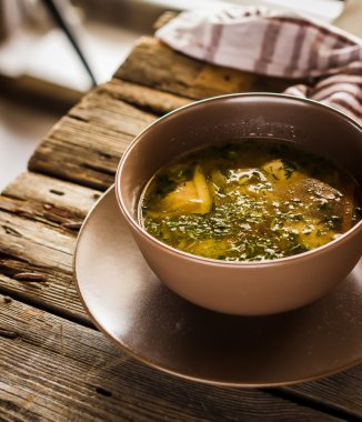 Bowl with  soup  on wooden table.