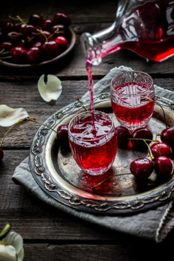 Cherry homemade liquor flowing in a vintage glass.