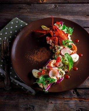 Salad with crawfish,shrimps,greens and radish on brown plate.
