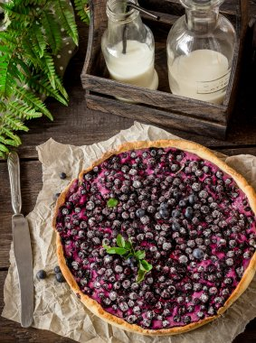Homemade pie with bilberry and milk on dark wooden table