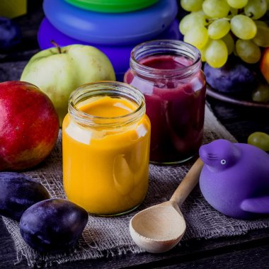 Baby food, fruits and toy on wooden table.