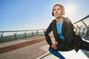 Cheerful woman exercising under music sounds outdoors