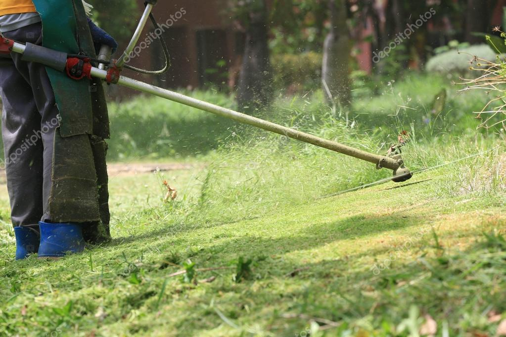 lawn mower worker cutting grass in green field