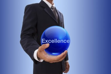 Businessman hand holding blue crystal ball with excellence word.