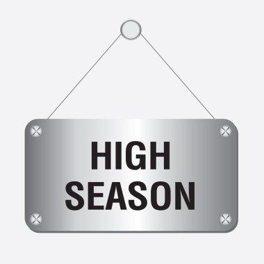 Silver metallic high season sign hanging on the wall