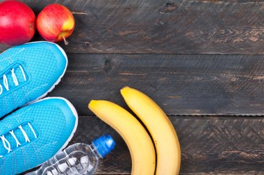Sport and healthy life. Sport shoes, apples, bananas and bottle