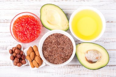 Healthy fats. Sources of omega 3 - avocado, olive oil, red caviar, nuts and flax seed on wooden background. Healthy food concept