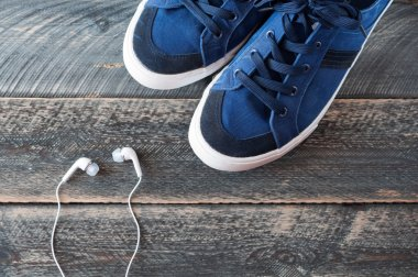 Sneakers and earphones on old wooden background