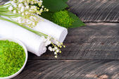 Natural green sea salt and towel for bath and spa on a wooden bo