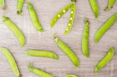 Pods of peas on a wooden background. Broad beans of peas backgro