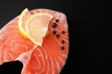 Fresh raw salmon steak red fish on a black background
