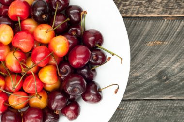 Cherries in a bowl on the old wooden background. Cherry backgrou