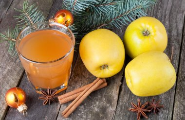 Apple juice in glass, apples, spices and fir on the old wooden b