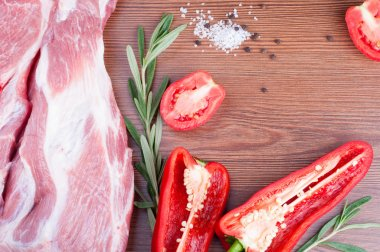 Raw meat with pepper, tomatoes, rosemary and spices on wooden ta