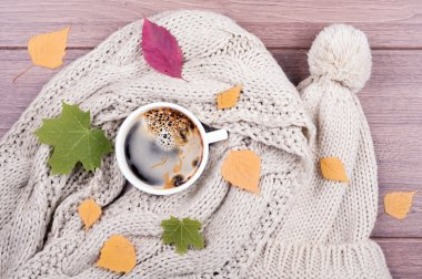Coffee cup, scarf and hat hand made, dry leaves on a wooden back