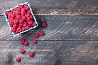 Raspberries in a basket on old wooden background. Rustic style