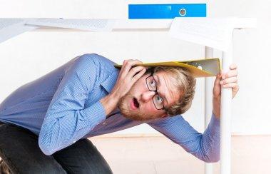 Employee hiding under a desk during an earthquake