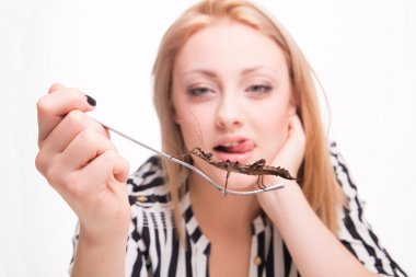 Joyful woman eating insects