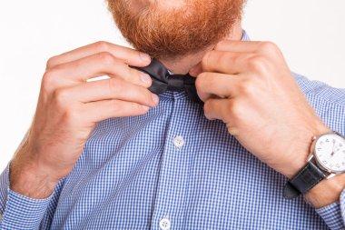 Bearded man tying a bow tie