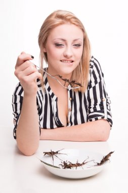 woman eating insects in restaurant