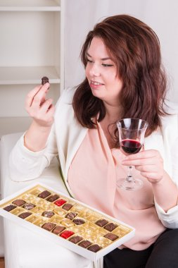 Plump woman with sweets and wine