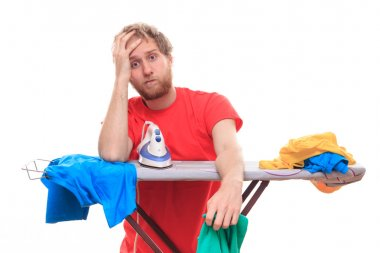 Embarassed man ironing on board