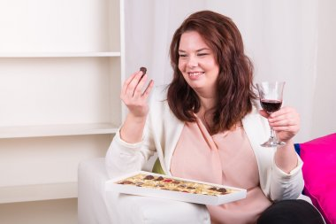 Plump woman eating chocolate with wine