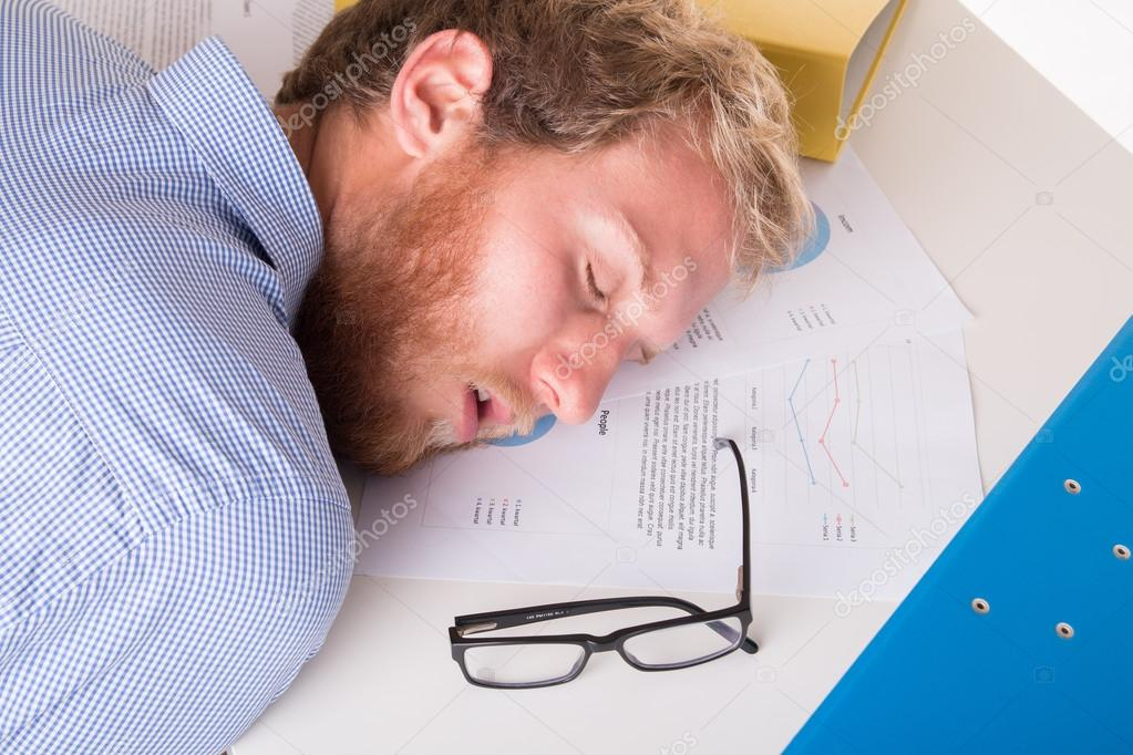 Worker sleeping on the desk in the office