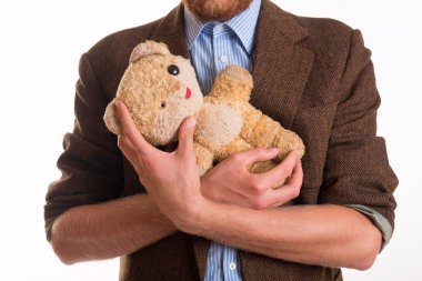 Old teddy bear in the arms of a man - studio shots stock vector