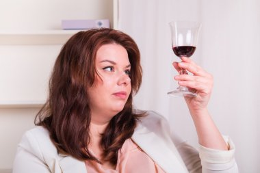 woman testing glass of red wine
